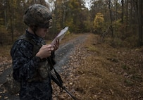 U.S. Navy Airman Timothy Lavergne, 305th Operations Support Squadron air traffic controller, checks a map during the 2018 Service Member of the Year Competition on Joint Base McGuire-Dix-Lakehurst, New Jersey, Nov. 5, 2018. Using a map, compass and protractor, the competitors had three hours to plot their route, locate four separate points and return to the starting point with all equipment. (U.S. Air Force photo by Airman 1st Class Ariel Owings)