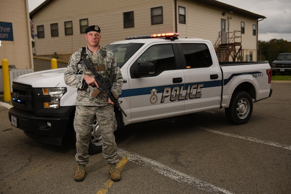 Master Sergeant Eric Moskal poses for a photo in front of a police truck.