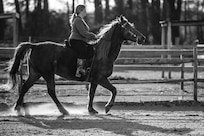 Tiffany Wisley, Langley Saddle Club head feeder, rides her horse Spooks at the stables on Joint Base Langley-Eustis, Virginia, April 11, 2018.