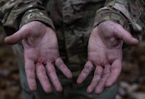 Sgt. 1st Class Mark Padifeld, 174th Infantry Brigade, 3rd Battalion, 314th Field Artillery Regiment fire support NCO observer and coach, shows his hands after the obstacle course during the 2018 Service Member of the Year Competition on Joint Base McGuire-Dix-Lakehurst, New Jersey, Nov. 6, 2018. U.S. Army Master Sgt. Juan Duque, Army Support Activity operation NCO, said the theme this year was to promote service members who can operate outside of their respective tasks within their sister services. (U.S. Air Force photo by Airman 1st Class Ariel Owings)