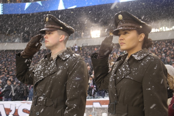 Soldier Models of the proposed Pink and Green daily service uniform display the outfits overcoat, as they render the hand salute during the National Anthem at Lincoln Financial Field in Philadelphia, Pennsylvania, during the Army-Navy Game December 9, 2017.
