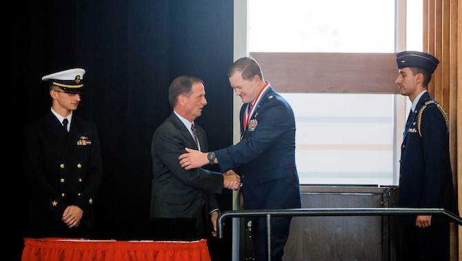 Lt. Col. TJ Eaton, reservist in the 419th Inspector General office, accepts a medal from Rep. Chris Stewart during a Veterans Day program Nov. 9 at the University of Utah.