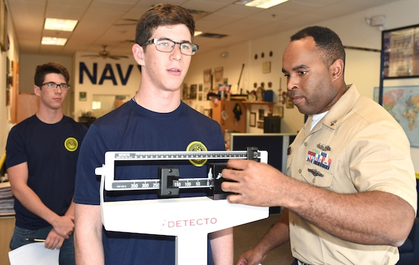 Petty Officer 1st Class Vincent Barnes of Chicago assigned to Navy Recruiting Station New Braunfels, Navy Recruiting District San Antonio conducts a height and weight measurements Oct. 30 of future Sailor Jack Lanier of Universal City, Texas, while his twin brother, James Lanier, observes during their 72-hour indoctrination at the NRS.  The Lanier brothers are seniors at Marion High School in Marion, Texas, and joined the Navy in the Nuclear Propulsion Program which currently is awarding bonuses of up to $40,000.