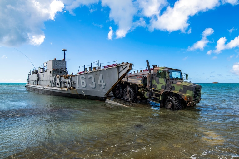 Soldiers drive an Army tactical vehicle off a Navy landing craft on a beach.