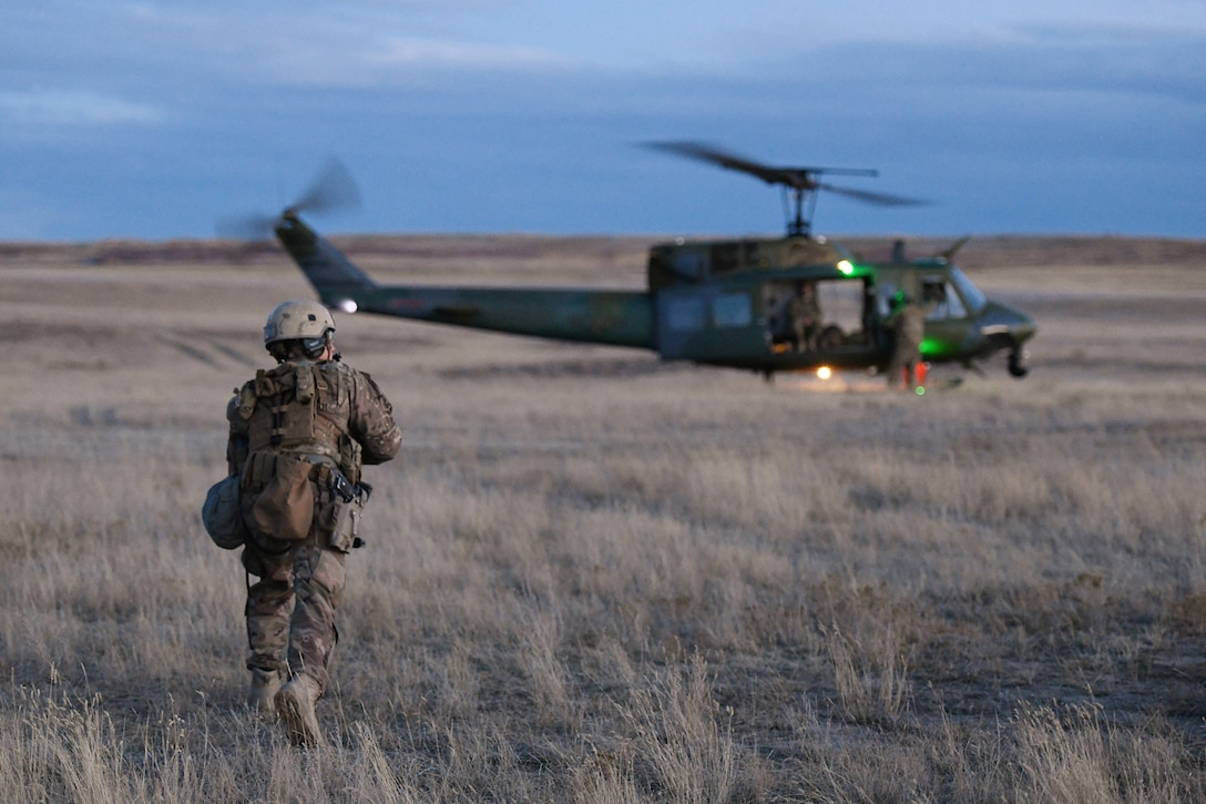 A member of the 341st Security Forces Group prepares to load a helicopter assigned to the 40th Helicopter Squadron during a launch facility recapture exercise during Global Thunder 19, Oct. 30, 2018, at Malmstrom Air Force Base, Mont.