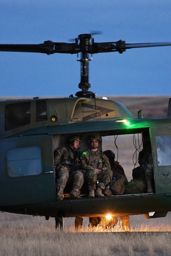 Members of the 341st Security Forces Group prepare to load a helicopter assigned to the 40th Helicopter Squadron during a launch facility recapture exercise during Global Thunder 19, Oct. 30, 2018, at Malmstrom Air Force Base, Mont.