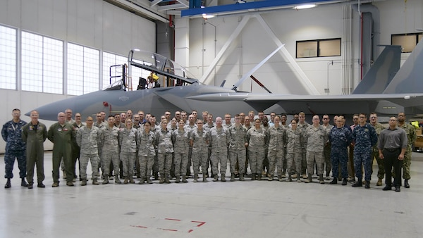 More than 50 service members stand in front of an F-15 on the factory floor.