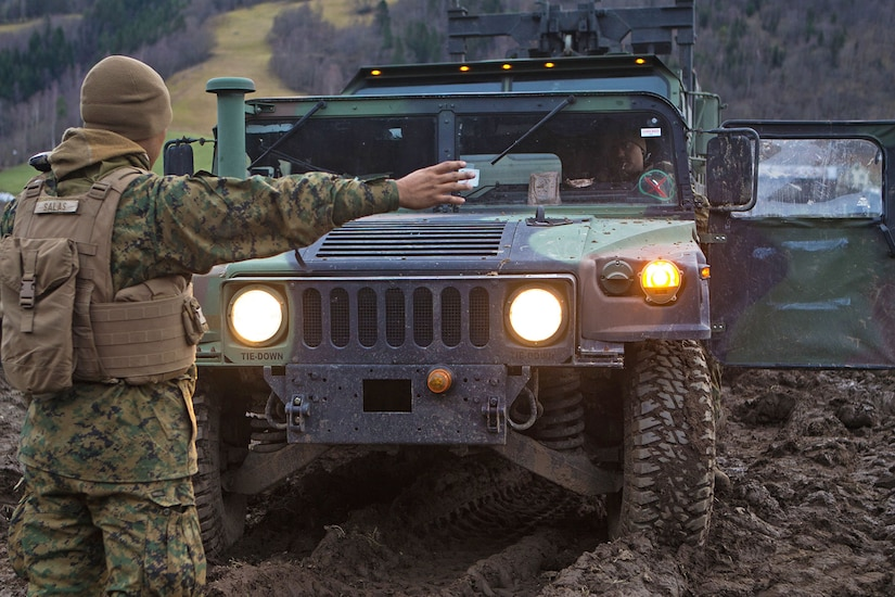 Marine directs vehicle operator in a muddy field