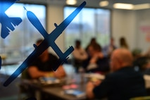 An MQ-9 Reaper sticker is displayed on a glass door while Airmen from the 432nd Wing/432nd Air Expeditionary Wing and the 799th Air Base Group participate in a spark cell workshop at AFWERX-Las Vegas Nov. 5, 2018. The visit brought together Airmen to collaborate, innovate, fabricate and present accelerated results to improve combat capabilities of the MQ-9 Reaper and the U.S. Air Force. (U.S. Air Force Photo by Airman 1st Class Haley Stevens)