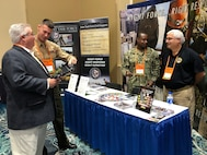 Marine Staff Sgt. Jordan Freking (middle left), Navy Chief Petty Officer Jean Isidore (middle right) and Mr. Michael Giles (right), members of Joint Task Force Civil Support, share and explain the command's mission to other chemical, biological, radiological and nuclear (CBRN) agencies at the 11th Annual CBRNe World Convergence in Orlando, Fla., on Nov. 7, 2018. The international convergence, which included representatives from over 30 different countries, gave JTF-CS an opportunity to connect and share information with other (CBRN) response leaders, as well as local first responders. It also allowed the command to see and test some of the newest anti-CBRN technology available.  When directed, JTF-CS is ready to respond in 24 hours to provide command and control of 5,200 federal military forces located at more than 36 locations throughout the nation in support of civil authority response operations to save lives, prevent further injury and provide critical support to enable community recovery. (Official DoD photo by Navy Lt. Cmdr. Jessica Caldwell/released)