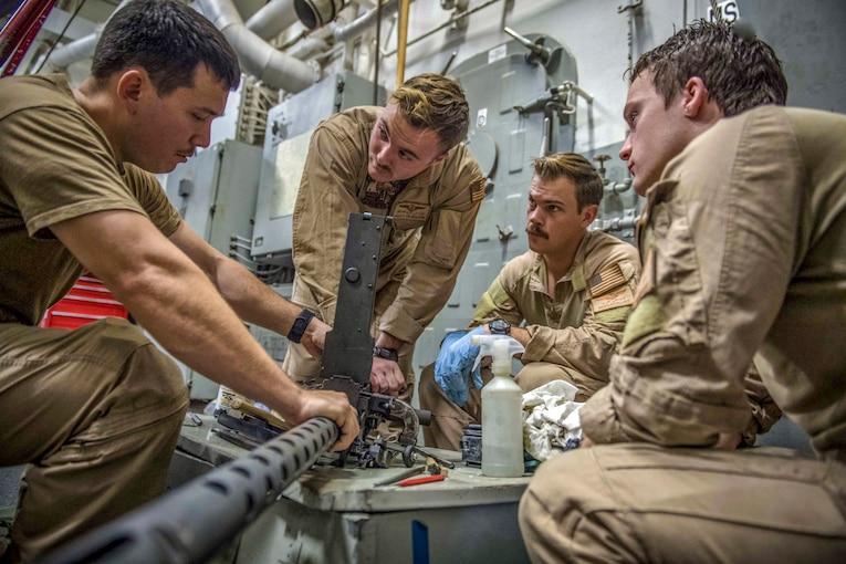A sailor demonstrates gun maintenance for other sailors.
