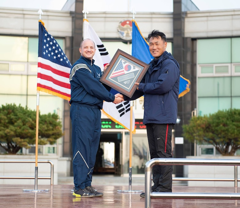 Col. John Bosone, 8th Fighter Wing commander (left), presents Col. Jae-Gyun Jeon, 38th Fighter Group commander (right), with a commemorative plaque at Kunsan Air Base, Republic of Korea, Nov. 9, 2018. The US-ROKAF Friendship Day focused on celebrating the partnership and alliance between the 8th Fighter Wing and 38th Fighter Group, who participated in several sporting events and competitions throughout the day. (U.S. Air Force photo by Senior Airman Stefan Alvarez)