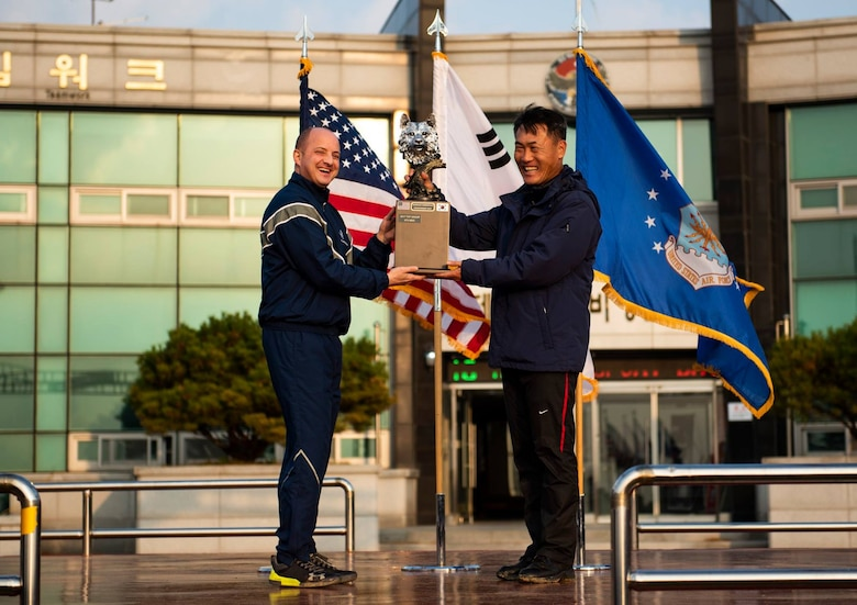 Col. John Bosone, 8th Fighter Wing commander (left), presents Col. Jae-Gyun Jeon, 38th Fighter Group commander (right), with the 2018 US-ROKAF Friendship Day trophy at Kunsan Air Base, Republic of Korea, Nov. 9, 2018. The US-ROKAF Friendship Day focused on celebrating the partnership and alliance between the 8th FW and 38th FG, who participated in several sporting events and competitions throughout the day. (U.S. Air Force photo by Senior Airman Stefan Alvarez)