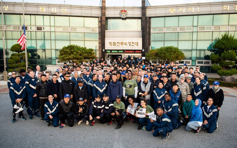 """8th Fighter Wing and 38th Fighter Group members pose for a group photo at Kunsan Air Base, Republic of Korea, Nov. 9, 2018. Participants of the 2018 US-ROKAF Friendship day competed in a variety of sports and interactive events, such as basketball, volleyball, the video game """"League of Legends,"""" golf, bowling, and soccer. (U.S. Air Force photo by Senior Airman Stefan Alvarez)"""
