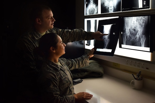 Senior Airmen Joseph Broyles and Sarai Eastman, 341st Medical Group diagnostic imaging technologists, examine X-rays at the clinic, Nov. 6, 2018, at Malmstrom Air Force Base, Mont. After the technicians review the X-rays for accuracy, they send the images to the radiologists at the Air Force Academy for further examination. (U.S. Air Force photo illustration by Airman 1st Class Jacob M. Thompson)