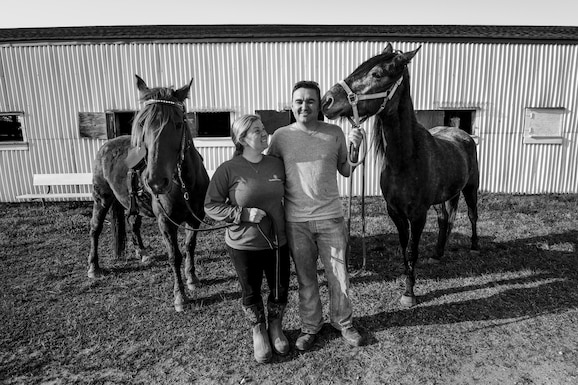 Tiffany Wisley, Langley Saddle Club head feeder, and U.S. Air Force Staff Sgt. Cody Wisley, 83rd Network Operations Squadron boundary protection supervisor, pose for a photo with their horses Spooks and Steel at the stables on Joint Base Langley-Eustis, Virginia, April 11, 2018.