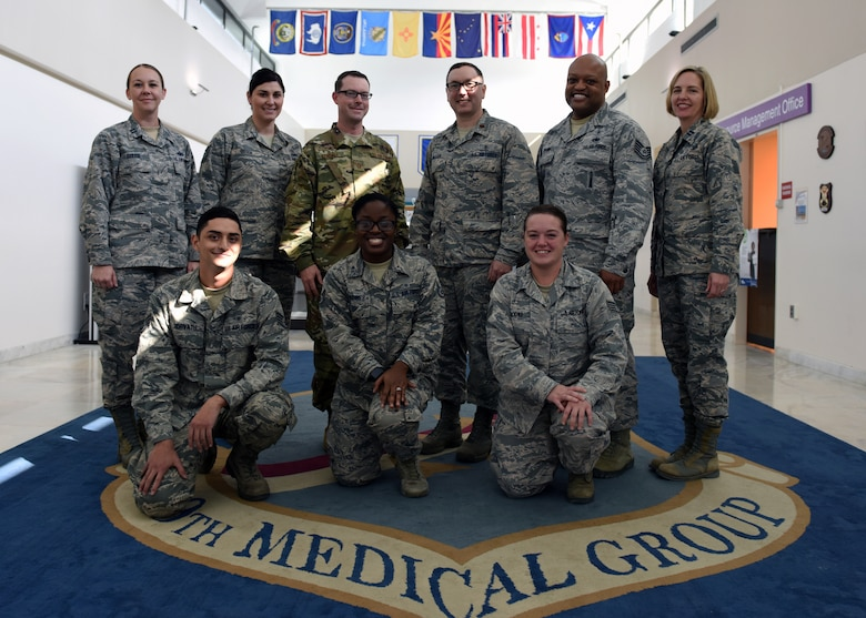 The Mental Health flight poses for a group photo in front of the 39th Medical Group shield at Incirlik Air Base, Turkey, Nov. 7, 2018.