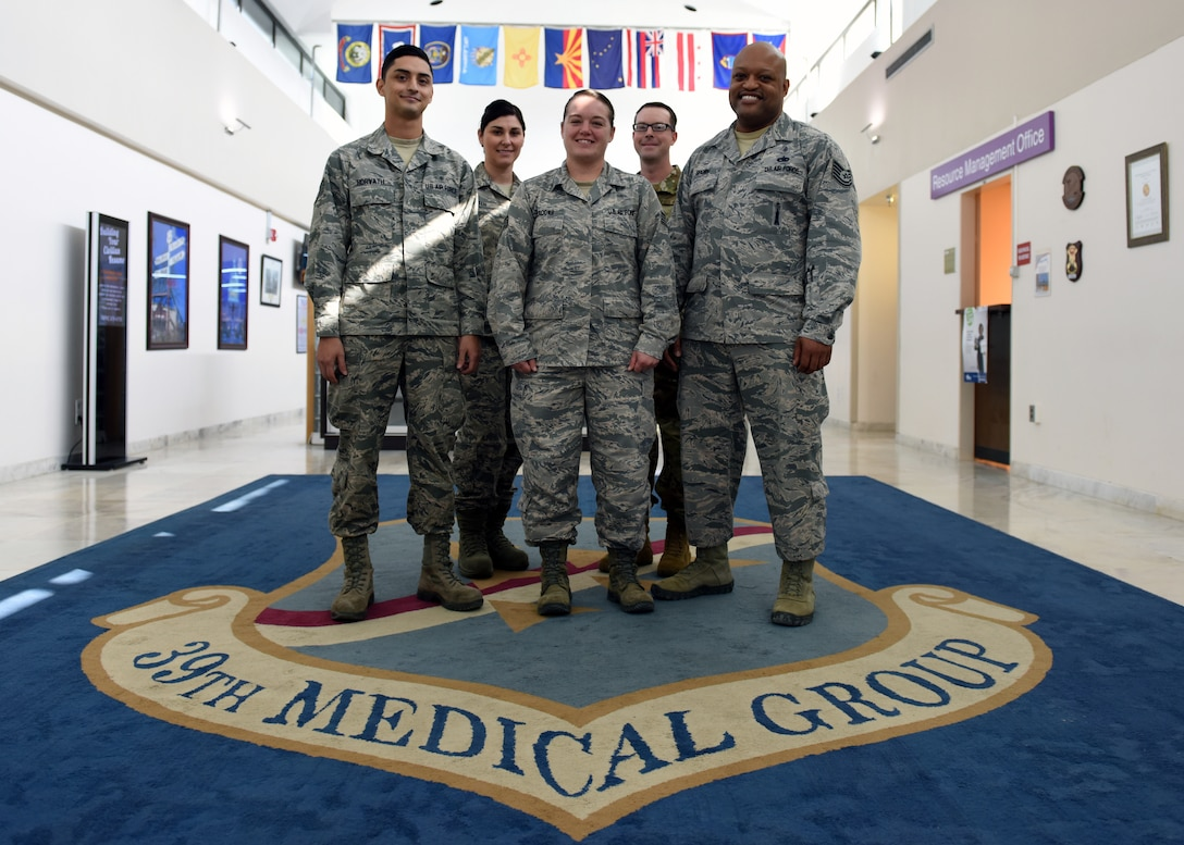 Mental health technicians assigned to the 39th Medical Operations Squadron pose in front of the 39th Medical Group shield at Incirlik Air Base, Turkey, Nov. 7, 2018.