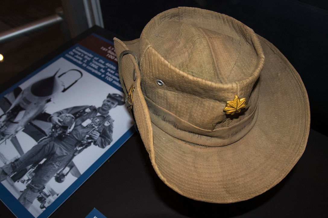 "DAYTON, Ohio - Lt. Col. Robert Krone's boonie hat. Attached to the hat is a Royal Thai Air Force pilot's badge. Also displayed in the case is his unusual trophy for completing a 100-mission tour. It reads ""First Commander with 100 Missions."" He flew a total of 125 combat missions in Southeast Asia. (U.S. Air Force photo by Ken LaRock)"