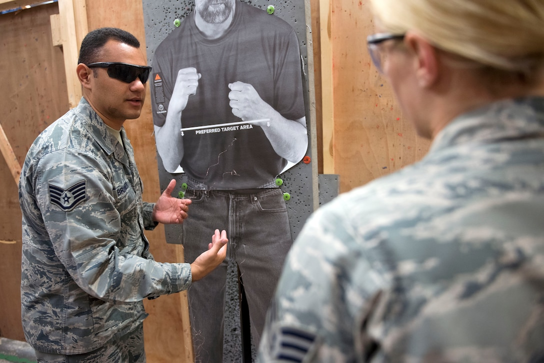 U.S. Air Force Staff Sgt. Anthony Bruner, 100th Security Force Squadron trainer, explains his evaluations of Senior Airman Olivia Krajca's shots at RAF Mildenhall, England, Nov. 8, 2018. At the minimum Airmen on duty are required to don a baton, and have the option to carry a Taser. (U.S. Air Force photo by Staff Sgt. Christine Groening)