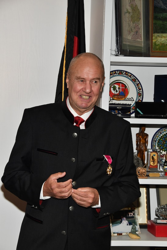 An Austrian army officer in civilian clothes speaks at an award ceremony.