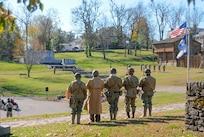 World War II reenactors stand at attention during the playing of Taps in Harrodsburg, Ky., Nov. 10, 2018. Soldiers with the Kentucky National Guard helped host a community-wide event honoring the Harrodsburg Tankers who endured the Bataan Death march in 1942.