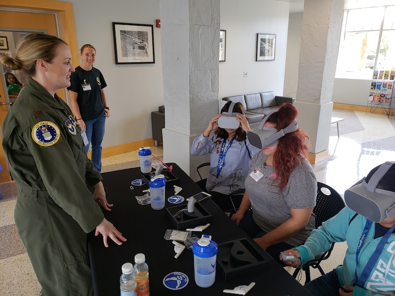 Maj. Lindsay Andrew, AFRS Det. 1 director of operations, demonstrates a VR headset with participants of Girls in Aviation Day.
