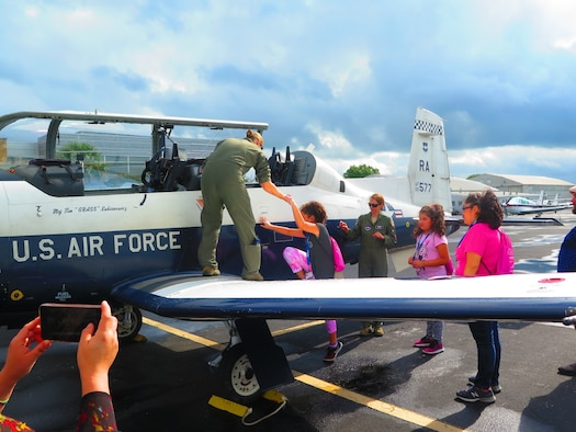Capt. Julie Rainwaters helps a young girl up onto the wing of a T-6 Texan II.