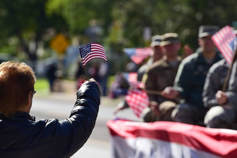 An attendee to Del Rio, Texas' Veterans Day Parade waves a flag towards a float of service members, Nov. 11, 2018. Laughlin Air Force, Base, Texas, and the local community of Del Rio, Texas, got together to celebrate all who have served through the town's tradition of a Veteran's Day Parade. The parade contained many floats featuring not only representatives of Laughlin, but also various veterans' organizations, vans and ROTC units.