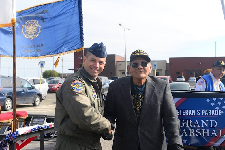 Col. Lee Gentile, 47th Flying Training Wing commander, shakes hands with a World War Two veteran during a Veteran's Day Parade at Del Rio, Texas, Nov. 11, 2018. Laughlin Air Force, Base, Texas, and the local community of Del Rio, Texas, got together to celebrate all who have served through the town's tradition of a Veteran's Day Parade. The parade contained many floats featuring not only representatives of Laughlin, but also various veterans' organizations, vans and ROTC units.