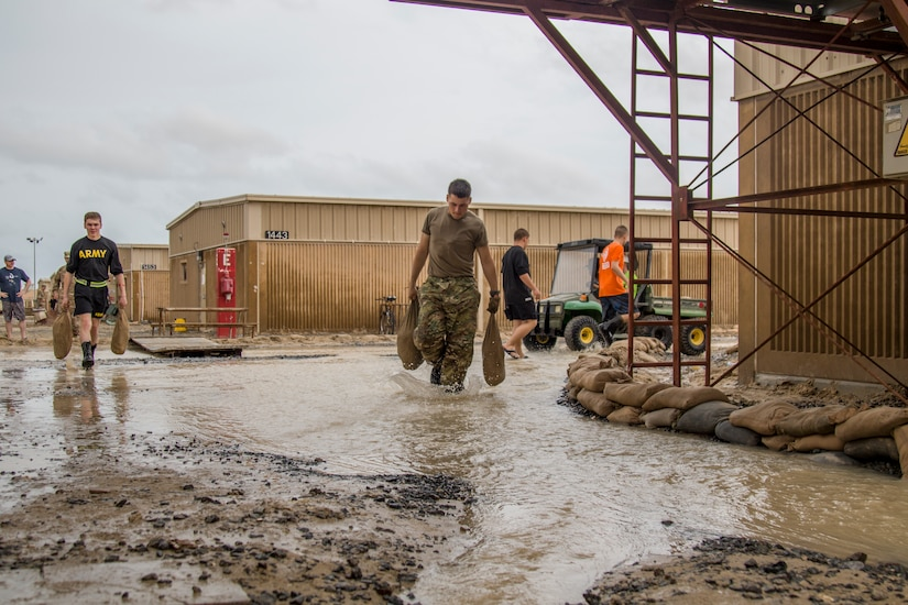 Soldiers carry sandbags through flood waters while constructing barriers following a rain storm at Camp Arifjan, Kuwait, November 15, 2018. Soldiers from multiple units joined together to respond to the flooding which had impacted their living quarters.