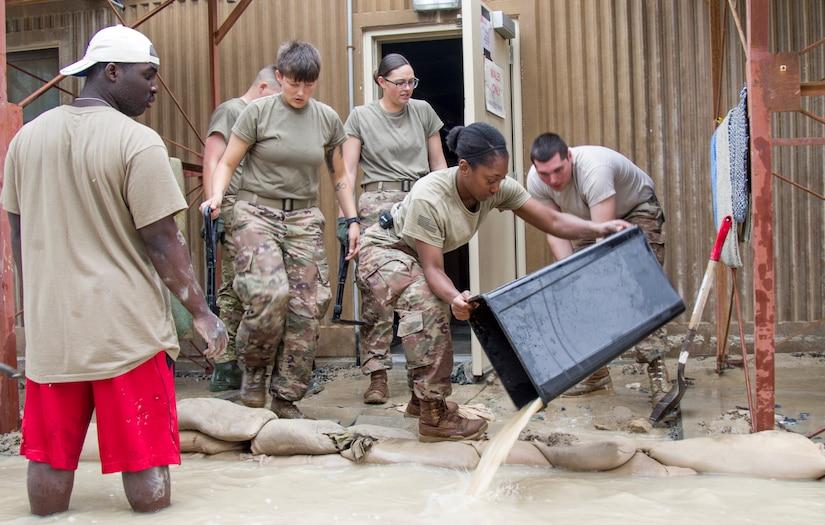 A Soldier uses a garbage can to bail water from behind a sandbag barrier in front of a barracks building following a severe rainstorm at Camp Arifjan, Kuwait, November 15, 2018. Soldiers from multiple units joined together to respond to the flooding which had impacted their living quarters.