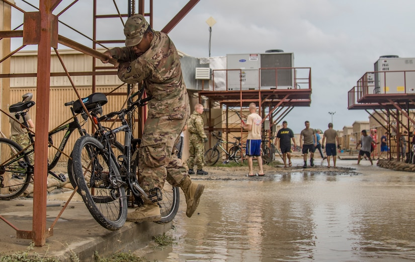 A Soldier clings to a metal structure to avoid flood waters outside of a barracks building at Camp Arifjan, Kuwait, November 15, 2018. The flooding came after an unusually heavy rainstorm hit the area, which has already experienced significant rain this month.