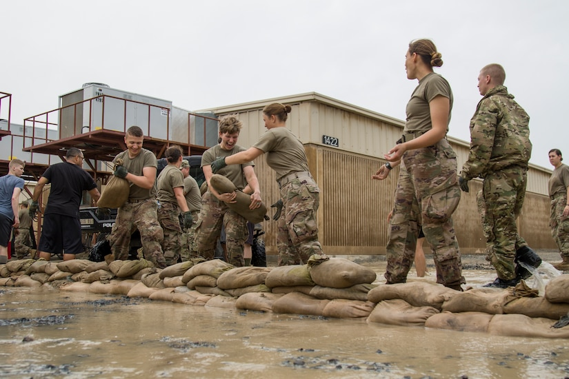 Soldiers pass sandbags to one another while building a barrier to control the floodwaters near their barracks at Camp Arifjan, Kuwait, November 15, 2018. The flooding came after an unusually heavy rainstorm hit the area, which has already experienced significant rain this month.