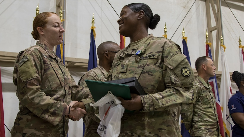 An instructor from the U.S. Army Central Noncommissioned Officer Academy congratulates Cpl. Markitta A. Carter during the graduation ceremony for class 18-710 of the U.S. Army Central Basic Leader Course, Oct. 17, 2018, at Camp Buerhing, Kuwait. The NCOA in Camp Buehring prepares junior Soldiers for leadership positions within their units while deployed overseas.