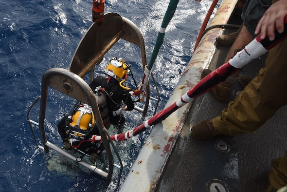 U.S. Navy Divers of Mobile Diving and Salvage Unit 2 prepare to lower the stage to conduct an underwater recovery operation in Italy.