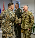 Master Sgt. Charles Barth, Grayling Air Gunnary Range, Mich., is decorated with the Commander of the Land Forces Medal for Merit, 3rd Class, at Ādaži Military Base, Latvia, Nov. 15, 2018. The awards were presented by Col. Ilmars Lejiņš, Land Forces Brigade Commander, National Armed Forces of Latvia. Ward and Barth received the honor for their contributions to the development of Latvia's Joint Tactical Air Controller program.