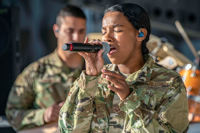 An airman holds a microphone and sings.