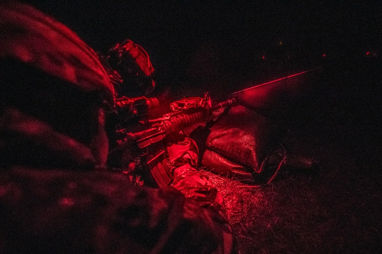 Soldiers crouch during live-fire training under the night sky.