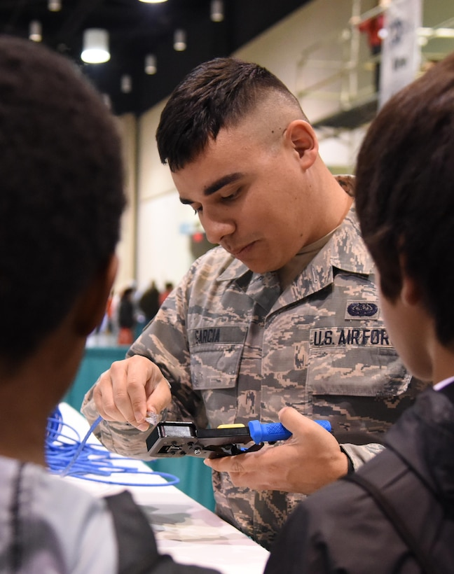 U.S. Air Force Senior Airman Romero Garcia, 81st Communications Squadron client systems technician, provides a demonstration on making cable from scratch to St. Martin Middle School students during the Pathways to Possibilities event at the Mississippi Coast Coliseum in Biloxi, Miss., Nov. 14, 2018. The event is an interactive career expo designed for all eighth graders in private and public schools in the six lower counties of Mississippi. The purpose of the event, set forth by the Mississippi Department of Education, is to help encourage a direction for the students high school pathway choice and is linked to the Common Core state standards. (U.S. Air Force photo by Kemberly Groue)