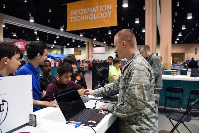 U.S. Air Force 2nd Lt. Colby Gilbert, 333rd Training Squadron cyber student, provides a cyber demonstration to St. Martin Middle School students during the Pathways to Possibilities event at the Mississippi Coast Coliseum in Biloxi, Miss., Nov. 4, 2018. The event is an interactive career expo designed for all eighth graders in private and public schools in the six lower counties of Mississippi. The purpose of the event, set forth by the Mississippi Department of Education, is to help encourage a direction for the students high school pathway choice and is linked to the Common Core state standards. (U.S. Air Force photo by Kemberly Groue)