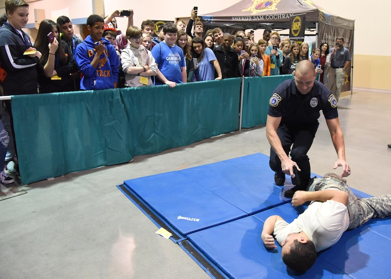 Justin DePew, 81st Security Forces Squadron unit trainer, conducts a stun gun demonstration on U.S. Air Force Senior Airman Daniel Anchondo, 81st Medical Operations Squadron medical technician, during the Pathways to Possibilities event at the Mississippi Coast Coliseum in Biloxi, Miss., Nov. 14, 2018. The event is an interactive career expo designed for all eighth graders in private and public schools in the six lower counties of Mississippi.  (U.S. Air Force photo by Kemberly Groue)