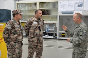 Airman talks to two Jordanian Air Force members in a fuel lab