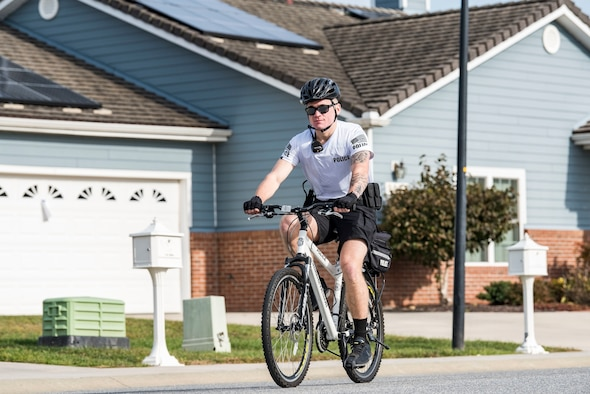 "Airman 1st Class Hunter Mowery, 436th Security Forces Squadron response force member, patrols the family housing area on his bicycle Oct. 25, 2018, at Dover Air Force Base, Del. Bike patrol members wear a highly-visible white shirt with ""police"" stenciled on the back, blue shorts, ride a mountain bike equipped with police lights and saddle bags with ""police"" stenciled on them"