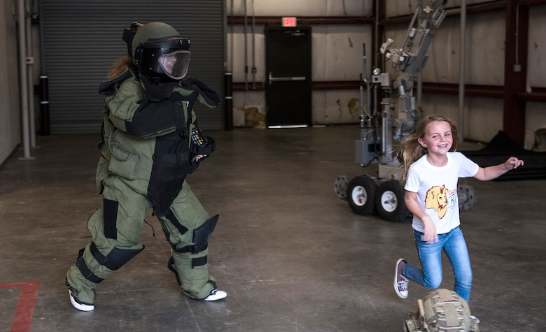 Fallon Emery, a new honorary member of the 437th Operations Support Squadron, chases her sister Mae while wearing an explosive ordnance disposal protective suit Nov. 7, 2018, at Joint Base Charleston, S.C., as part of the Airman for a Day program.