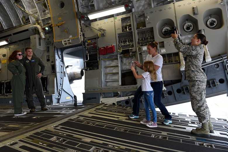 Fallon Emery, a new honorary member of the 437th Operations Support Squadron, poses for photos with 1st Lt. Thad Sollick, a C-17 Globemaster III pilot assigned to the 437th OSS, inside a C-17 Nov. 7, 2018, at Joint Base Charleston, S.C., as part of the Airman for a Day program.