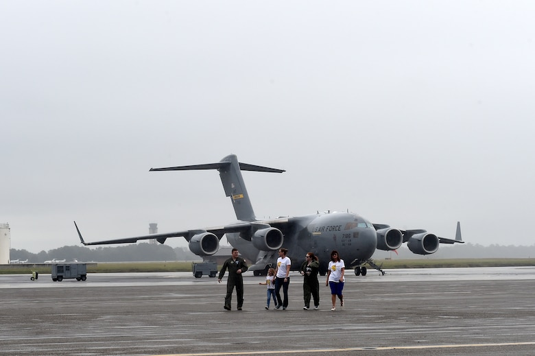 Fallon Emery, second from right, a new honorary member of the 437th Operations Support Squadron, walks on the flight line with 1st Lt. Thad Sollick, left, a C-17 Globemaster III pilot assigned to the 437th OSS, Nov. 7, 2018, after touring a C-17 at Joint Base Charleston, S.C., as part of the Airman for a Day program.