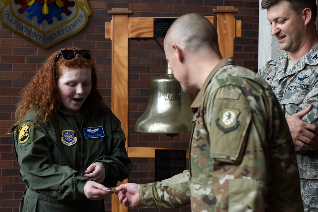 Fallon Emery, a new honorary member of the 437th Operations Support Squadron, accepts a challenge coin from Chief Master Sgt. Ronnie Phillips, 437th Airlift Wing command chief master sergeant, Nov. 7, 2018, at Joint Base Charleston, S.C., as part of the Airman for a Day program.