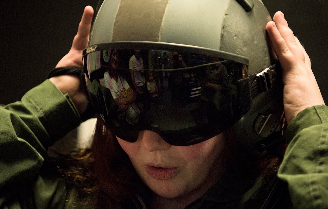Fallon Emery, a new honorary member of the 437th Operations Support Squadron, tries on a flight helmet at the Aircrew Flight Equipment facility Nov. 7, 2018, at Joint Base Charleston, S.C., as part of the Airman for a Day program.