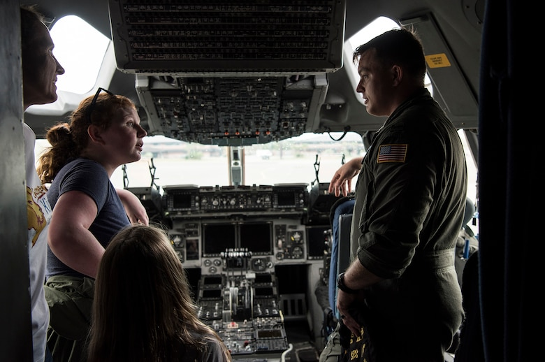 1st Lt. Thad Sollick, a C-17 pilot assigned to the 437th Operations Support Squadron, briefs Fallon Emery, a new honorary member of the 437th OSS, and her family inside the cockpit of a C-17 Globemaster III aircraft Nov. 7, 2018, at Joint Base Charleston, S.C., as part of the Airman for a Day program.